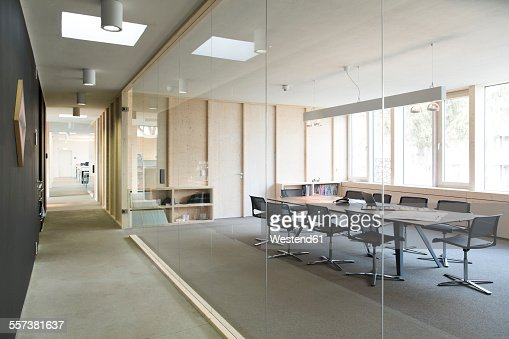 Corridor and modern conference room separated by glass pane