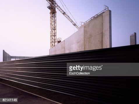 Corrugated metal fence with construction site at dawn.
