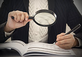 "Corruption audit concept. Inspector using magnifying glass for inspect budget corruption.""n"