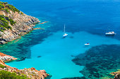Corsica, French island in Mediterranean Sea. Coastal summer landscape, yachts moored in azure bay