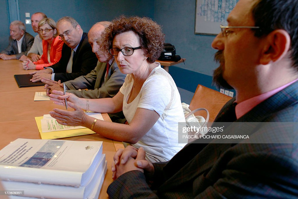 Corsican doctor Alessio Pittidis (R) hands over a report on the alleged spread of radioactive fallout from the May 1986 Chernobyl disaster over the French Corsican island to (CtoL) member of the executive council Maria Guidicelli, Corsican Assembly President Dominique Bucchini and Corsica executive council president Paul Giacobbi on July 4, 2013.