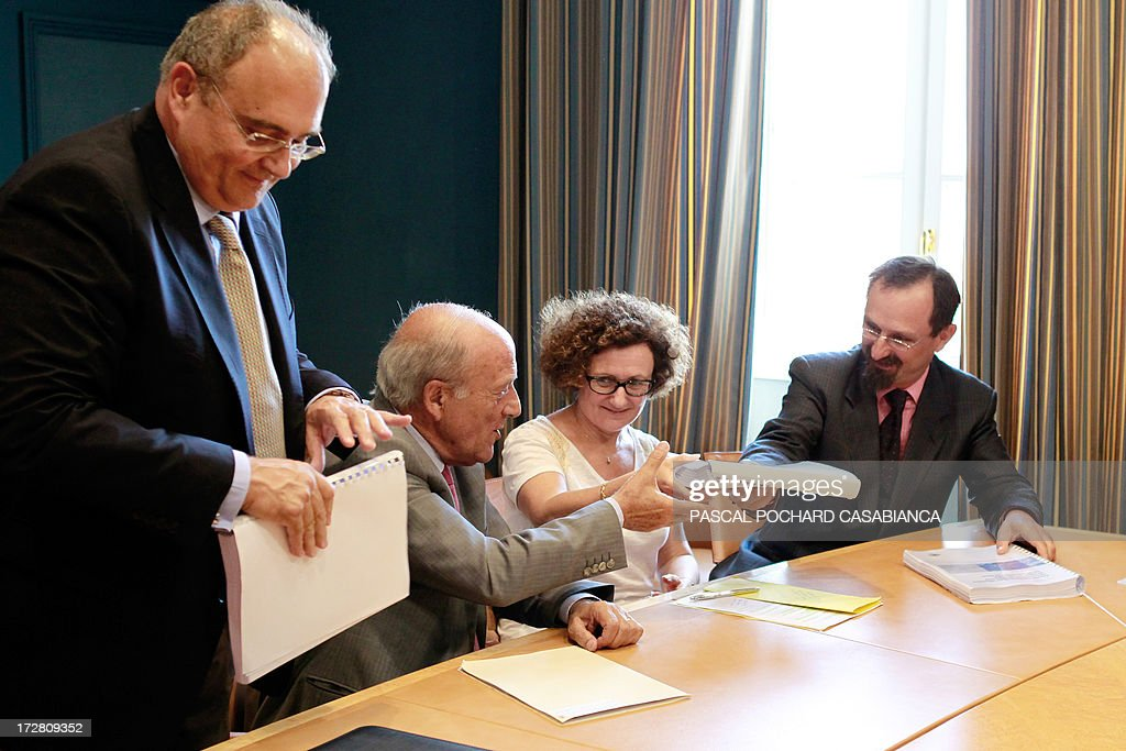 Corsican doctor Alessio Pittidis (R) hands over a report on the alleged spread of radioactive fallout from the May 1986 Chernobyl disaster over the French Corsican island to (LtoR) Corsica executive council president Paul Giacobbi, Corsican Assembly President Dominique Bucchini and member of the executive council Maria Guidicelli, on July 4, 2013.