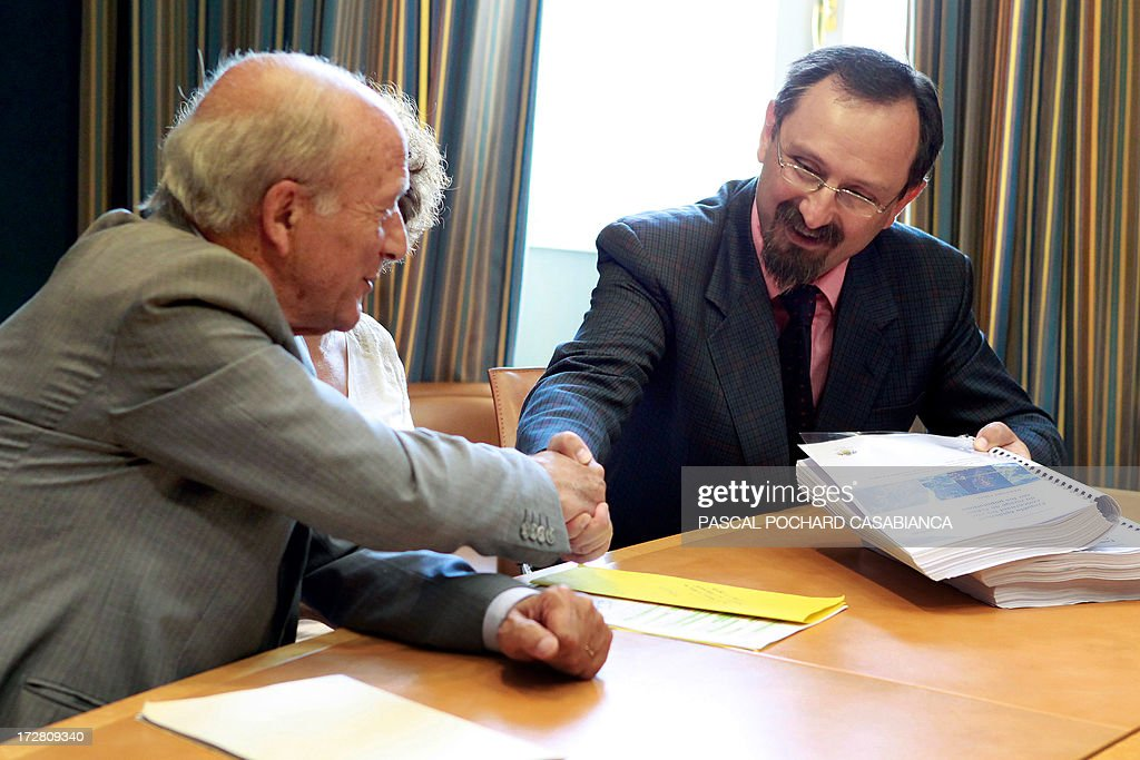 Corsican doctor Alessio Pittidis (R) shakes hands with Corsican Assembly President Dominique Bucchini as he hands over a report on the alleged spread of radioactive fallout from the May 1986 Chernobyl disaster over the French Corsican island on July 4, 2013.