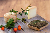 Corsican traditional varity of goat cheese with arbitus bay on a wooden background