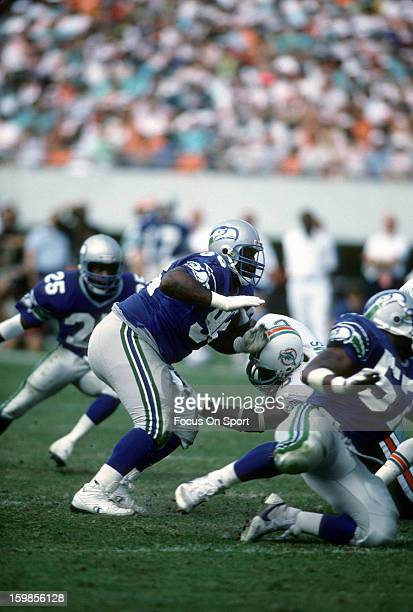 Cortez Kennedy of the Seattle Seahawks rushes up against Keith Sims of the Miami Dolphins during an NFL football game December 16 1990 at Joe Robbie...