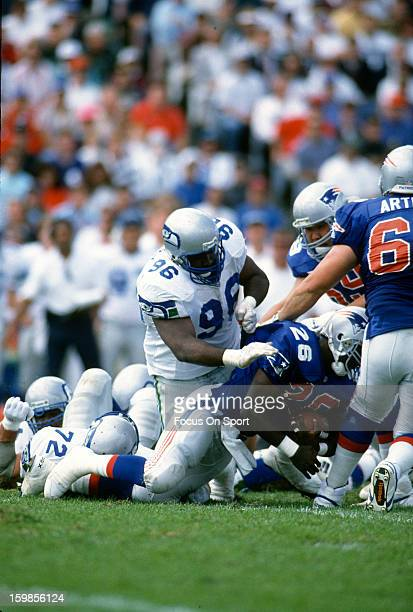 Cortez Kennedy of the Seattle Seahawks tackles Corey Croom of the New England Patriots during an NFL football game September 19 1993 at Foxboro...