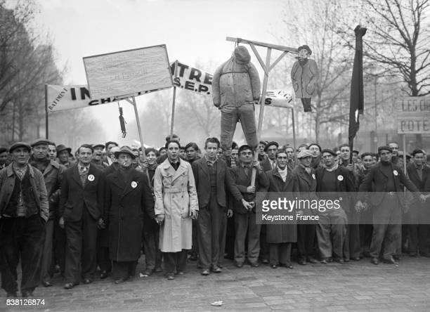 Cortège de manifestants brandissant pendus et pancartes devant l'entrée des abattoirs de La Villette protestant contre l'insuffisance et la cherté de...