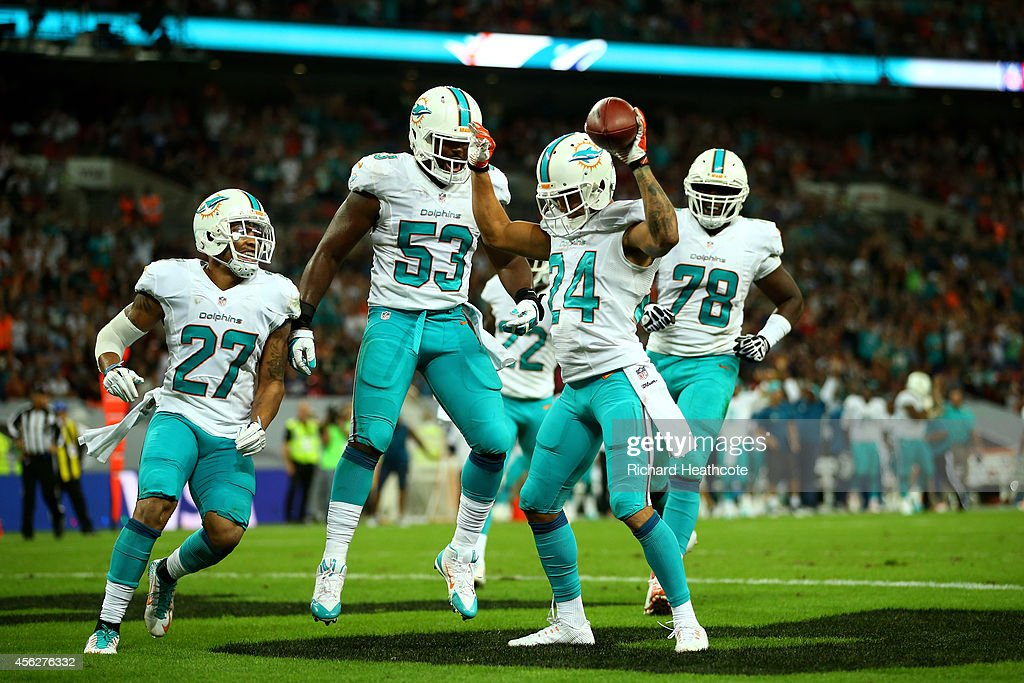 Cortland Finnegan #24 of the Miami Dolphins celebrates with teammates after returning a fumble 50 yards to score a touchdown during the NFL match between the Oakland Raiders and the Miami Dolphins at Wembley Stadium on September 28, 2014 in London, England.