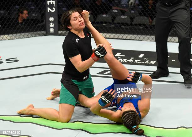 Cortney Casey upkicks Jessica Aguilar in their women's strawweight fight during the UFC 211 event at the American Airlines Center on May 13 2017 in...