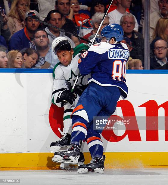 Cory Conacher of the New York Islanders hits Trevor Daley of the Dallas Stars into the boards at the Nassau Veterans Memorial Coliseum on October 25...