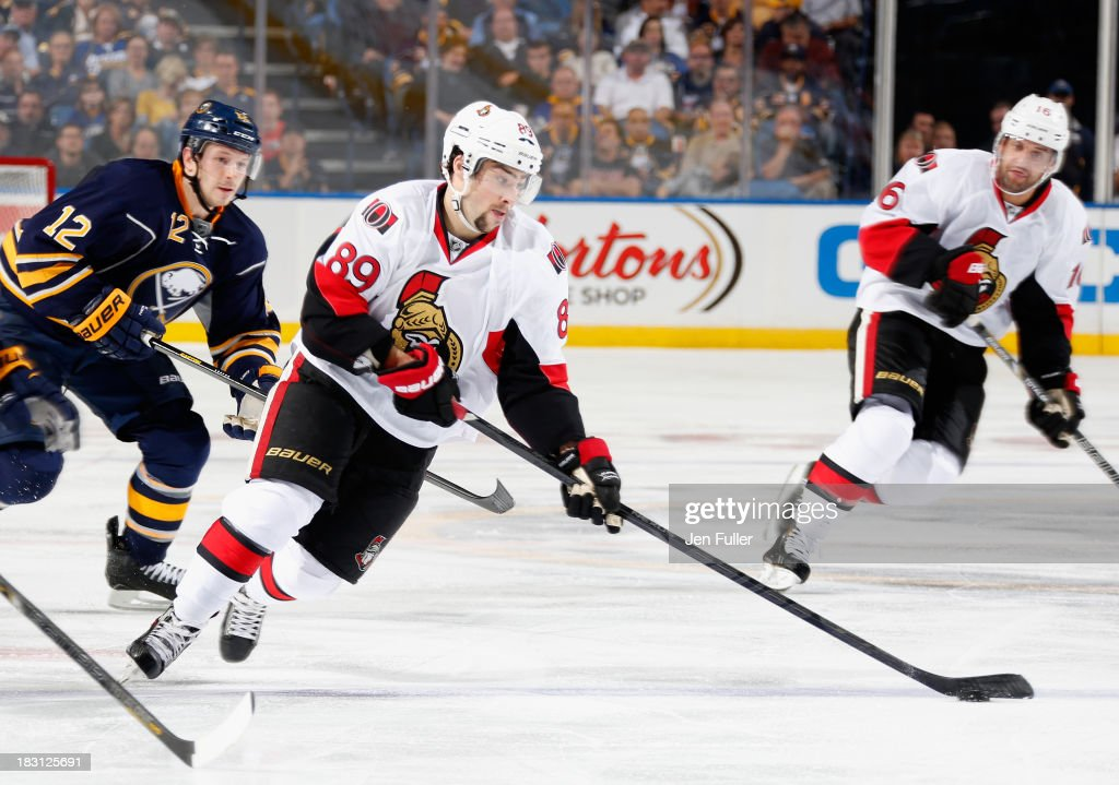 Cory Conacher #89 of the Ottawa Senators carries the puck in front of teammate Clarke MacArthur #16 and Kevin Porter #12 of the Buffalo Sabres at First Niagara Center on October 4, 2013 in Buffalo, New York. Ottawa defeated Buffalo 1-0.
