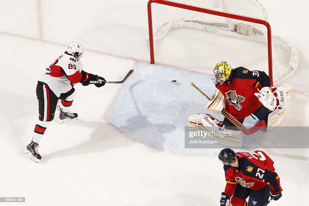 <a gi-track='captionPersonalityLinkClicked' href=/galleries/search?phrase=Cory+Conacher&family=editorial&specificpeople=8312407 ng-click='$event.stopPropagation()'>Cory Conacher</a> #89 of the Ottawa Senators scores a first period goal against goaltender <a gi-track='captionPersonalityLinkClicked' href=/galleries/search?phrase=Scott+Clemmensen&family=editorial&specificpeople=214674 ng-click='$event.stopPropagation()'>Scott Clemmensen</a> #30 of the Florida Panthers at the BB&T Center on April 7, 2013 in Sunrise, Florida. The Panthers defeated the Senators 2-1.