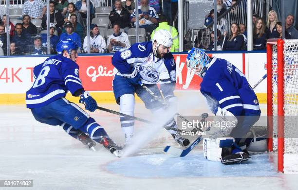 Cory Conacher of the Syracuse Crunch is stopped by goalie Kasimir Kaskisuo of the Toronto Marlies as Travis Dermott of the Marlies helps defend...