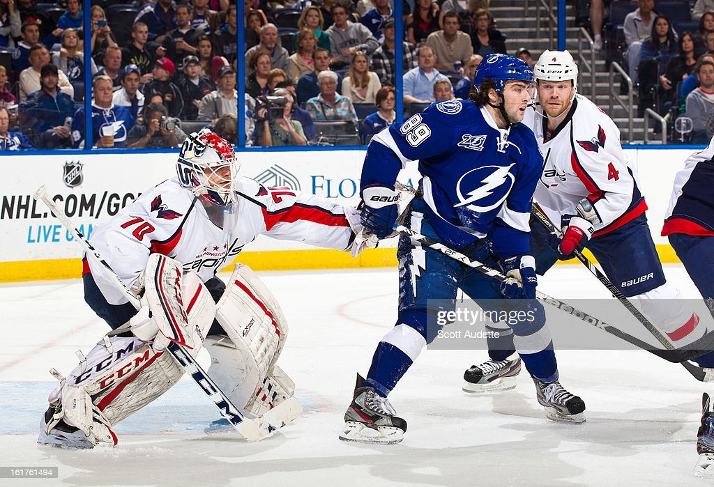 Cory Conacher #89 of the Tampa Bay Lightning stands outside the play blocking John Erskine #4 of the Washington Capitals during the third period of the game at the Tampa Bay Times Forum on February 14, 2013 in Tampa, Florida.