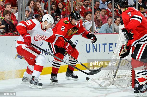 Cory Emmerton of the Detroit Red Wings and Duncan Keith of the Chicago Blackhawks battle for the puck in Game Seven of the Western Conference...