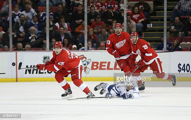 Cory Emmerton of the Detroit Red Wings flips the puck out of the zone as David Clarkson of the Toronto Maple Leafs stretches goes for a deflection...