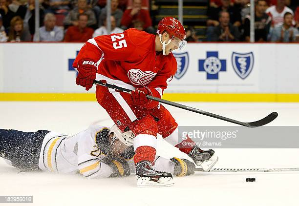 Cory Emmerton of the Detroit Red Wings is tripped up by Thomas Vanek of the Buffalo Sabres in the second period at Joe Louis Arena on October 2 2013...