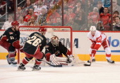 Cory Emmerton of the Detroit Red Wings looks to slip the puck past goaltender Jason LaBarbera of the Phoenix Coyotes as Derek Morris and Steve...