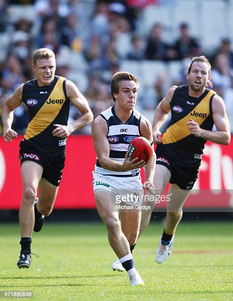 Cory Gregson of the Cats runs with the ball away from Taylor Hunt of the Tigers and Jake Batchelor during the round five AFL match between the...