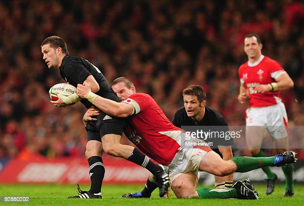 Cory Jane of New Zealand is tackled by Matthew Rees of Wales during the Invesco Perpetual Series match between Wales and New Zealand at Millennium...
