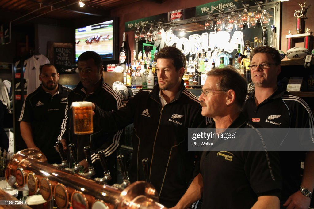Cory Jane of the All Blacks (C) delivers a pint for a punter at the Mornington Tavern watched by John Afoa and Sitiveni Sivivatu on July 19, 2011 in Dunedin, New Zealand.