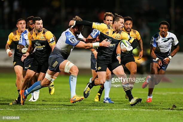Cory Jane of the Hurricanes attempts to fend Ben McCalman of the Force during the round four Super Rugby match between the Hurricanes and the Force...