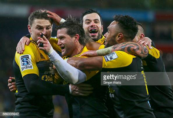 Cory Jane of the Hurricanes celebrates a try with teammates Beauden Barrett and James Marshall during the 2016 Super Rugby Final match between the...