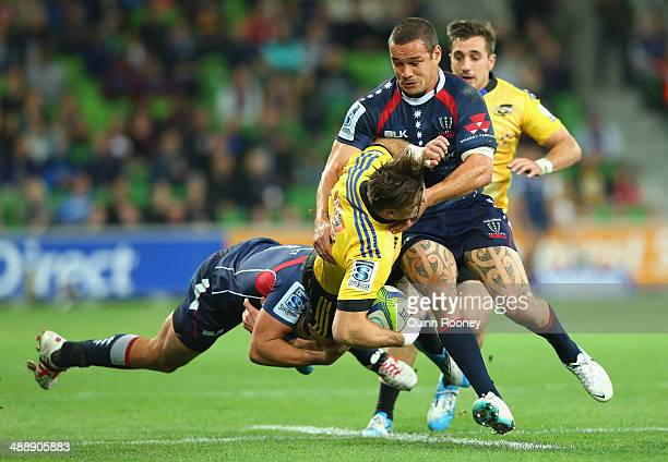 Cory Jane of the Hurricanes is tackled by Tom English and Tamati Ellison of the Rebels during the round 13 Super Rugby match between the Rebels and...