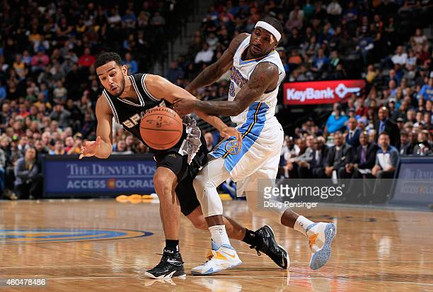 Cory Joseph of the San Antonio Spurs and Ty Lawson of the Denver Nuggets collide as they go for the ball at Pepsi Center on December 14 2014 in...