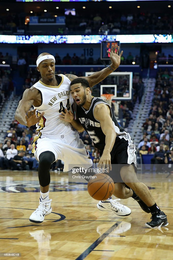 Cory Joseph #5 of the San Antonio Spurs drives the ball around Dante Cunningham #44 of the New Orleans Pelicans at Smoothie King Center on December 26, 2014 in New Orleans, Louisiana.
