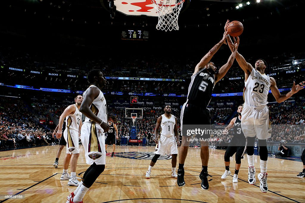 Cory Joseph #5 of the San Antonio Spurs jumps for a rebound against Anthony Davis #23 of the New Orleans Pelicans on December 26, 2014 at Smoothie King Center in New Orleans, Louisiana.