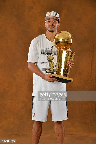 Cory Joseph of the San Antonio Spurs poses for a portrait with the Larry O'Brien Trophy after defeating the Miami Heat in Game Five of the 2014 NBA...
