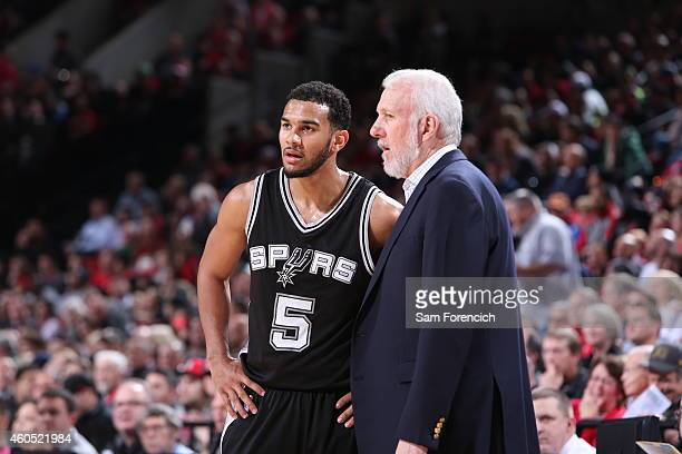 Cory Joseph of the San Antonio Spurs talks with Head Coach Gregg Popovich during the game against the Portland Trail Blazers on December 15 2014 at...