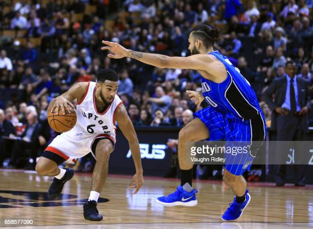 Cory Joseph of the Toronto Raptors dribbles the ball as Evan Fournier of the Orlando Magic defends during the second half of an NBA game at Air...