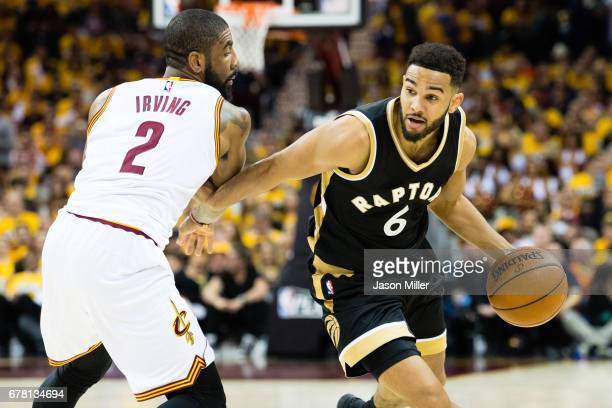Cory Joseph of the Toronto Raptors drives around Kyrie Irving of the Cleveland Cavaliers during the second half of Game Two of the NBA Eastern...