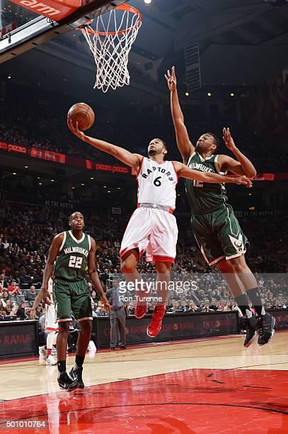 Cory Joseph of the Toronto Raptors shoots the ball against Jabari Parker of the Milwaukee Bucks on December 11 2015 at the Air Canada Centre in...