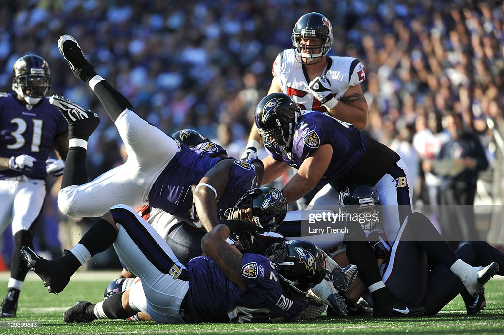 Cory Redding #93 of the Baltimore Ravens helps make a tackle against the Houston Texans at M&T Bank Stadium on October 16. 2011 in Baltimore, Maryland. The Ravens defeated the Texans 29-14.