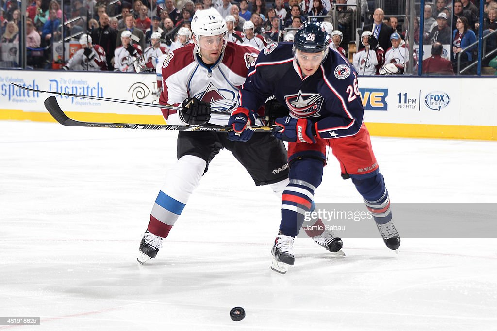 Cory Sarich #16 of the Colorado Avalanche and Corey Tropp #26 of the Columbus Blue Jackets skate after a loose puck during the third period on April 1, 2014 at Nationwide Arena in Columbus, Ohio. Colorado defeated Columbus 3-2 in overtime.