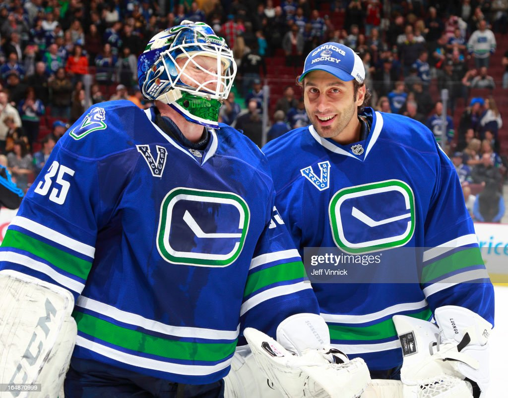 Cory Schneider # 35 and Roberto Luongo #1 of the Vancouver Canucks skate of the ice together after defeating the Colorado Avalanche in their NHL game at Rogers Arena March 28, 2013 in Vancouver, British Columbia, Canada. Vancouver won 4-1.