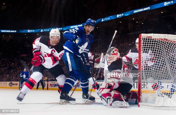 Cory Schneider of the New Jersey Devils and teammate Andy Greene tie up James van Riemsdyk of the Toronto Maple Leafs during the first period at the...