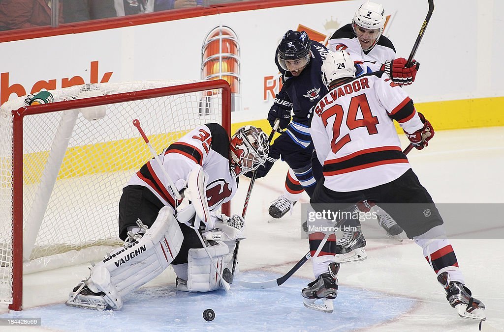 <a gi-track='captionPersonalityLinkClicked' href=/galleries/search?phrase=Cory+Schneider&family=editorial&specificpeople=696908 ng-click='$event.stopPropagation()'>Cory Schneider</a> #35 of the New Jersey Devils blocks a shot on goal by <a gi-track='captionPersonalityLinkClicked' href=/galleries/search?phrase=Evander+Kane&family=editorial&specificpeople=4303789 ng-click='$event.stopPropagation()'>Evander Kane</a> #9 of the Winnipeg Jets as <a gi-track='captionPersonalityLinkClicked' href=/galleries/search?phrase=Marek+Zidlicky&family=editorial&specificpeople=203291 ng-click='$event.stopPropagation()'>Marek Zidlicky</a> #2 and Bryce Salvador #24 try to get in for the rebound in third period action of an NHL game at the MTS Centre on October 13, 2013 in Winnipeg, Manitoba, Canada.