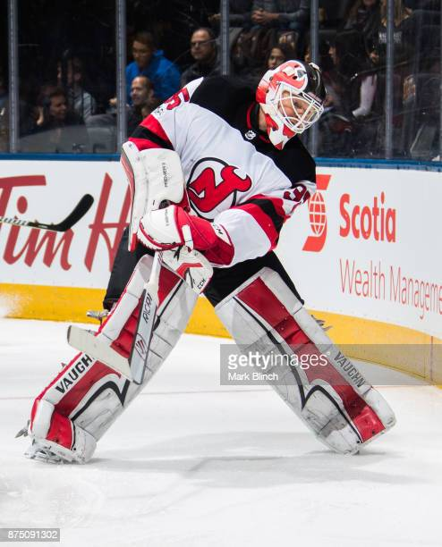 Cory Schneider of the New Jersey Devils clears the puck during the first period against the Toronto Maple Leafs at the Air Canada Centre on November...
