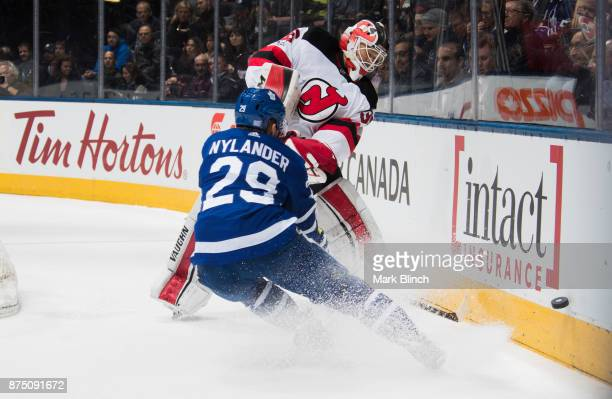 Cory Schneider of the New Jersey Devils clears the puck part William Nylander of the Toronto Maple Leafs during the first period at the Air Canada...