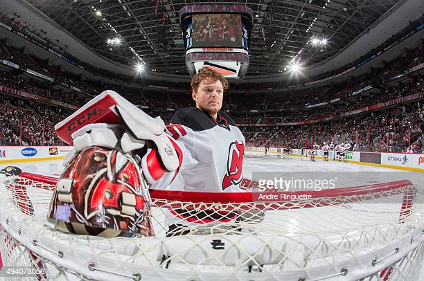 Cory Schneider of the New Jersey Devils grabs his mask from off the top of his net prior to a game against the Ottawa Senators at Canadian Tire...