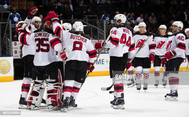 Cory Schneider of the New Jersey Devils is congratulated by his teammates after defeating the Toronto Maple Leafs at the Air Canada Centre on October...