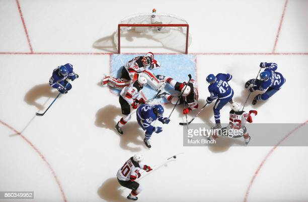 Cory Schneider of the New Jersey Devils is surrounded by teammates Blake Coleman Jesper Bratt John Moore and Mirco Mueller in addition to Tyler Bozak...