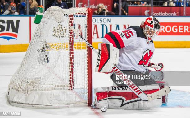 Cory Schneider of the New Jersey Devils makes a save against the Toronto Maple Leafs during the third period at the Air Canada Centre on October 11...