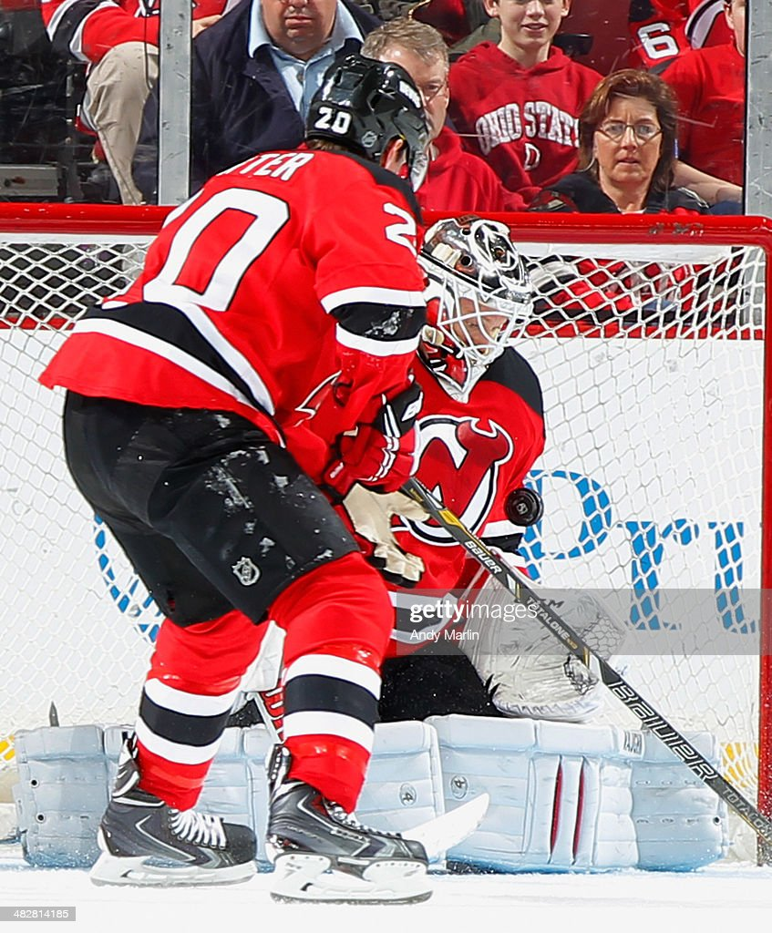 <a gi-track='captionPersonalityLinkClicked' href=/galleries/search?phrase=Cory+Schneider&family=editorial&specificpeople=696908 ng-click='$event.stopPropagation()'>Cory Schneider</a> #35 of the New Jersey Devils makes a save as <a gi-track='captionPersonalityLinkClicked' href=/galleries/search?phrase=Ryan+Carter+-+Ice+Hockey+Player&family=editorial&specificpeople=3144941 ng-click='$event.stopPropagation()'>Ryan Carter</a> #20 looks to clear the rebound against the Washington Capitals during the game at the Prudential Center on April 4, 2014 in Newark, New Jersey.