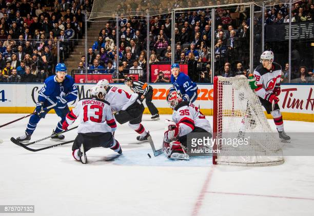 Cory Schneider of the New Jersey Devils makes a save as teammates Nico Hischier John Moore and Damon Severson defend against William Nylander and Leo...