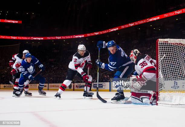 Cory Schneider of the New Jersey Devils makes a save on Leo Komarov of the Toronto Maple Leafs as Ben Lovejoy of the New Jersey Devils defends during...